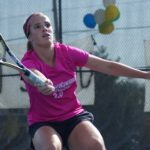 Tennis player watches ball
