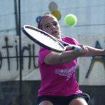 Girl hits tennis ball