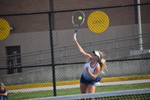 Emma serves ball
